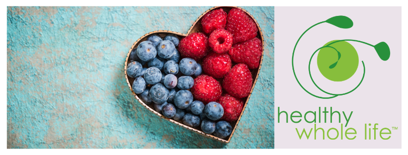 blue background heart with blueberries raspberries